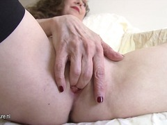 Horny mature gal fingering on the bed.