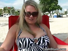 Blonde amateur flashing her big tits on a beach.