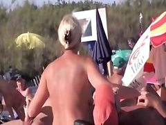 French naturist woman strokes cocks of two men on nudist beach.